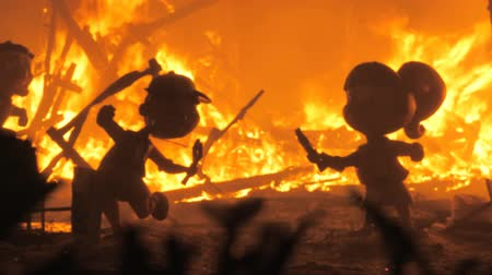 кукла : VALENCIA, SPAIN - MARCH 19, 2019: Two doll figures surrounded by fire during the Las Fallas feast in Valencia