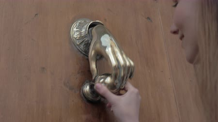 bater : A detail with a silver door handle in the form of hand, a womans hand takes it and knocks - Valencia, Spain Stock Footage