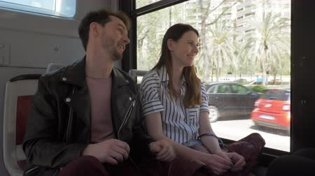 conta : A young couple travelling by bus and communicating pleasantly