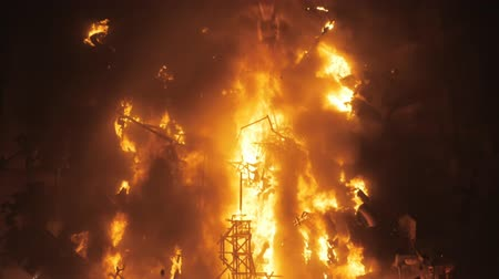 fete : A burning installation with doll figures during the Las Fallas feast in Valencia, camera unzooms to the wide shot