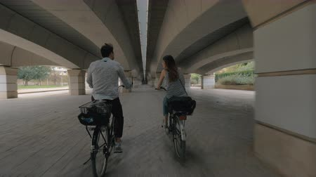 Валенсия : A young couple on bicycles, riding under a wide bridge construction. We see them from the back