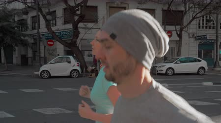 gündelik : Steadicam shot of young and active couple having a jog together. Everyday morning run in the city streets