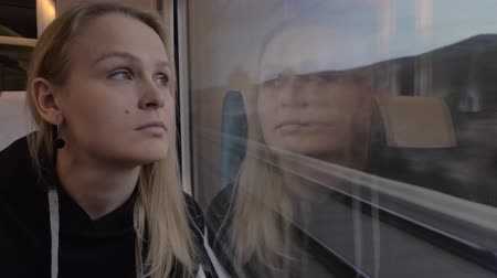 wistful : Young blond woman enjoying landscapes in the window of moving train. Railway journey Stock Footage