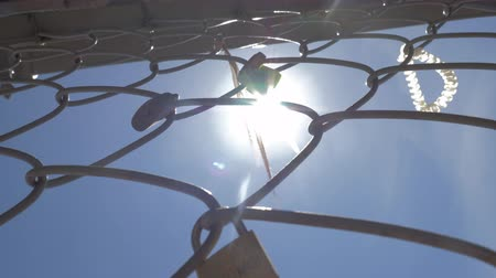 맹꽁이 자물쇠 : Love padlocks and ribbons left on the metal wire mesh, view against the sky with bright sunshine 무비클립