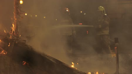 arriscado : Slow motion shot of several unidentified firemen fighting fire at night