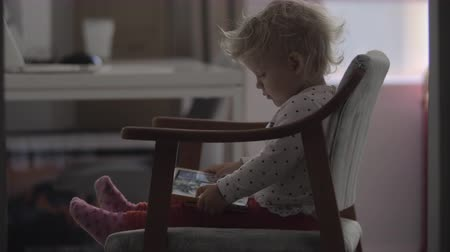 use computer : Two year old child is attracted with cartoons. Little girl sitting on the chair with digital tablet and staring at the screen. Indoor leisure