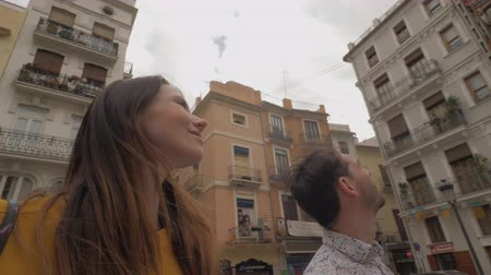casal : Steadicam shot of young couple walking in the street of Valencia and looking at architecture around them. Visiting Spain