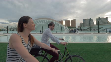 Валенсия : Steadicam shot of young couple enjoying bike ride through the city. Happy man and woman cycling near City of Arts and Sciences in Valencia, Spain
