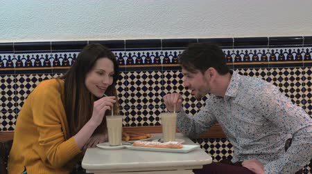 испанский : Young man and woman visiting cafe in Valencia and tasting horchata served with fartons and churros