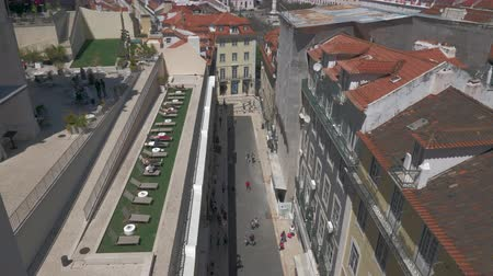 teszi : Lisbon cityscape with street, houses and rooftop terrace with chaise longues. View from Santa Justa Lift, Portugal