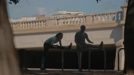 keep fit : Young man and woman working out outdoors in the city and doing stretching exercises