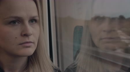 wistful : Close-up shot of young woman traveling by train and being deep in thought. Her reflection in window overlaying the scenes outside