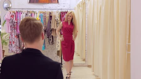 obyčejný : Beautiful young blonde showing red dress to her boyfriend in dressing room