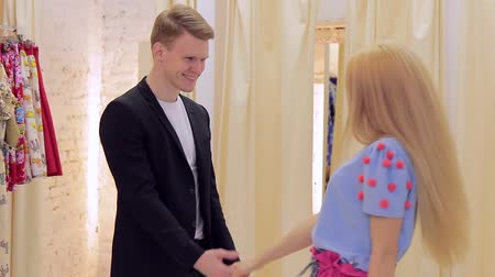 obyčejný : Happy young couple having fun chooses clothes in a the fitting room