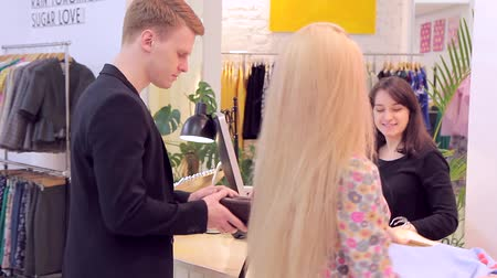 продавец : Beautiful caucasian couple choose clothes in the store and goes to cash-desk Стоковые видеозаписи