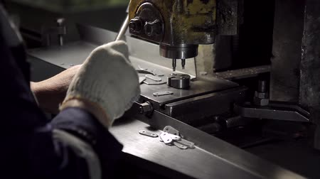 fasteners : Hands work on a machine for the manufacture small metal fasteners