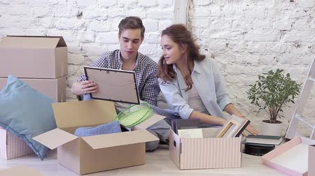 жилье : Smiling couple with cardboard boxes moving to new home