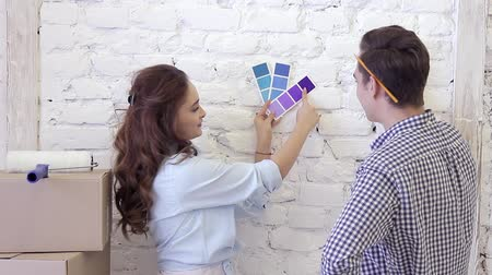 repaint : Young couple and color swatches to select a wall decoration