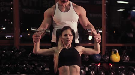 levantamento de pesos : Young woman and her personal fitness trainer in the gym with dumbbells Vídeos