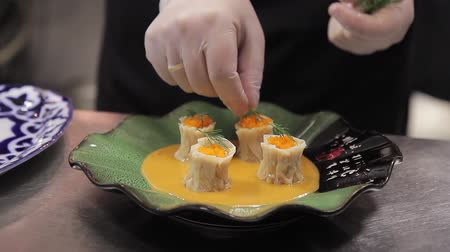 gunkan : Chef finishing dish to serve at table On green design plate like flower. Rolls of dough with caviar in carrot sauce dressing course with green dill.