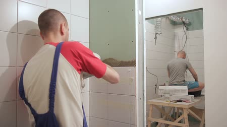 banyo : Young master cleans putty from wall standing indoors. He uses spatula to remove remnants Stok Video