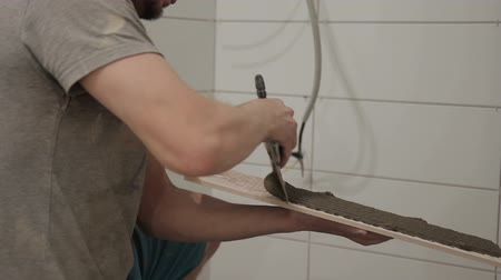 kielnia : A man applies a trowel to one tile that will cover the walls. The man in the overalls squats Wideo