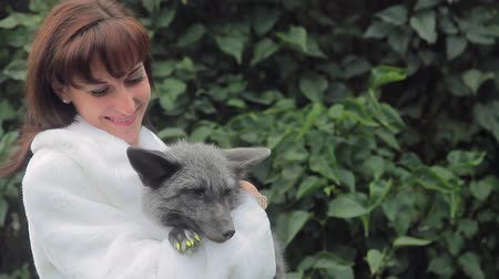 zsír : Young woman is holding gray fox standing near green tree in summer. Female poses, holding in hands adult pet and looking forward, with friendly smile, locating in verdant park.