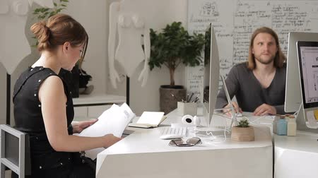 corporate affairs : Woman in office collects documents in one pile among staff at desk. Two employees are engaged in important affairs with paper and communicate with each other. Stock Footage