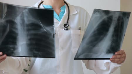 compares : Doctor with a stethoscope examines two X-rays of human chest. Medical officer in uniform in hospital compares several results of a fluorographic survey.