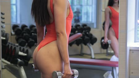 atleta : Woman in swimsuit with bare hips holding a dumbbell in fitness. Attractive lady with a sexy figure trains with sports equipment in front of a mirror in gym. Vídeos