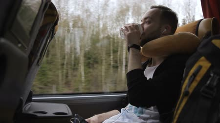 otobüs : Unshaven man drinks coffee during a bus trip in spring. Weary traveler picks up a glass and takes a sip during long journey by road transport. Stok Video