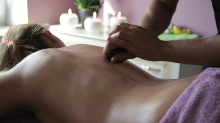 kamień : On female back professional circulates skin in circular motion. Against background of burning candles procedure is performed to relax spine in spa. Wideo