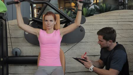 eğitici : Sportswoman is training arms and her personal male instructor is observing the exercising in the gym.