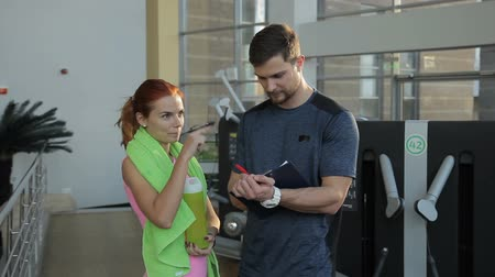 eğitici : In gym trainer interrogates woman to compose a personal training program. Woman with a towel around her neck answers instructors questions for the service questionnaire. Stok Video