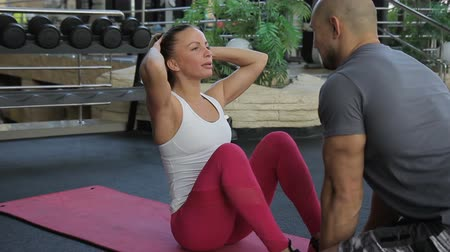 eğitici : The male trainer helps his female student to do sit-ups in the luxury gym. The woman wears white top and trousers and lies on the pink mat during the exersices. Stok Video