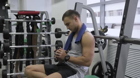 ivászat : Young bodybuilder shakes shaker and drinks whey cocktail in sports club indoors. Man jiggles container and takes sip of chocolate beverage. Attractive person with watch on his wrist sits on bench among iron equipment in modern gym after intense workout an Stock mozgókép