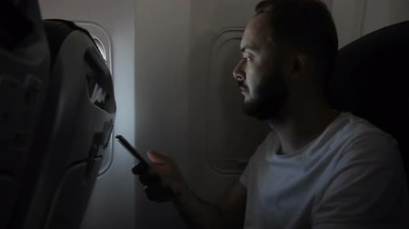 utas : Portrait of young man, who is using his smartphone in the aircraft. Male passenger with beard and in white t-shirt is sitting on confortable chair near the closed window and scrolling the screen of his brand-new device. Stock mozgókép