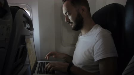 utas : Young guy works with laptop while sitting on airplane. Handsome businessman is in working process during flight, using pc. Confident bearded rustler types text, tapping his fingers on keyboard and looking at display carefully. Internet access allows him t Stock mozgókép