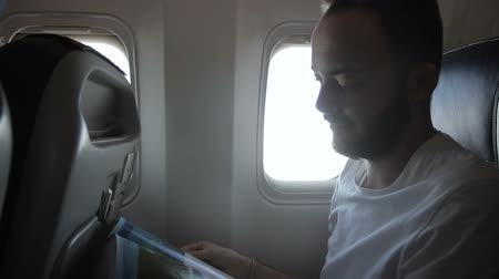 utas : Portrait of male passenger, who is reading magazine in the modern aircraft. Man in white t-shirt and with beard is sitting on comfortable seat, near the window and enjoying his travel by plane while turning the pages of the journal.