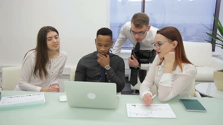 относящийся к разным культурам : At office desk in office multi-ethnic team with a leader looks at laptop. Four female and male employees of a large company with African American and European people are brainstorming at computer together with their leader.