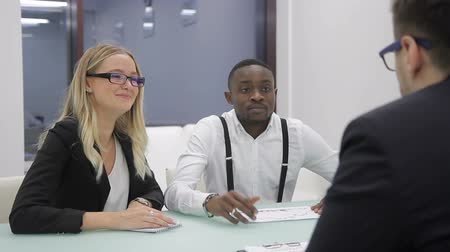 относящийся к разным культурам : Three multi-ethnic people are having a business negotiations in modern office. African financial analytic, blond woman are sitting at the table and discussing the strategy with their partner in glasses.