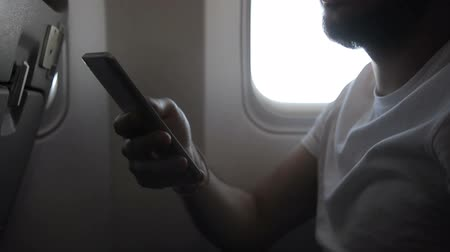 utas : Hand of young man holding smartphone in the plane, close up. Male passenger with beard, in white t-shirt, is scrolling down the screen of his brand-new device while sitting on the seat in modern aircraft.