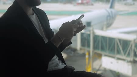 bagagem : Businessman is typing text on the screen of his smartphone in the airport. Man in black jacket is sitting near the big window with a nice view to the airside with planes and using his brand-new device while waiting for the departure. Vídeos