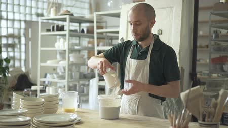 hrnčíř : Young master immerses mug in liquid at desk pottery workshop. Man is standing at table and puts cup in container with water indoors. Bearded guy is in working process in light room with shelves on which there are many ceramic products. Person dressed in w