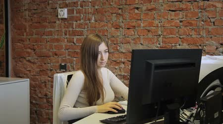 corporate affairs : Female specialist looking at computer screen sitting in modern office Stock Footage