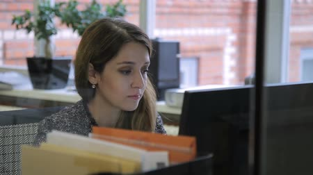 el emeği göz nuru : Female employee looks at computer screen while sitting at desk in office. Brunette reads attentively information on pc screen, propping face against hand. Young specialist, performs working tasks carefully and concentrated, not being distracted by extrane