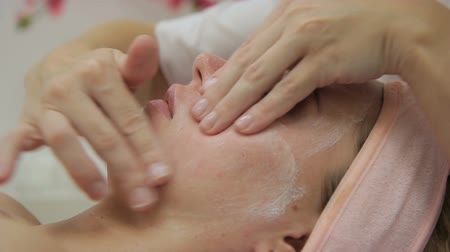 посылка : Cosmetologist does facial massage to woman in beauty salon. Female massages neatly, cleansed skin of young client, who lies in relaxed pose with closed eyes. Experienced specialist cares for delicate skin gently, touching it with soft movement, previously