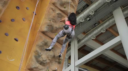 rock wall : Beautiful woman comes down on insurance from climbing wall on bouldering. Female athlete in sports equipment joyfully completes training and gently slides on rope. Stock Footage