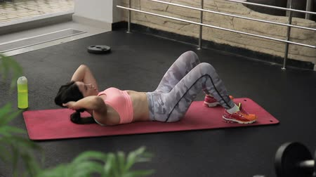 pumping : Woman on mat trains and carefully pumps press on stomach in gym. Beautiful female brunette lies and raises and lowers body for development of abdominal muscles during fitness.