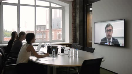 プレゼンテーション : Employees hold meeting through video conferencing on plasma. Three women sit at table with large monitor, through which they communicate with manager in business suit and glasses.